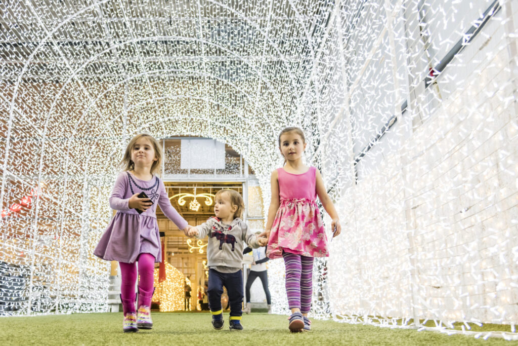 Two girls and a boy walking through a tunnel of light.