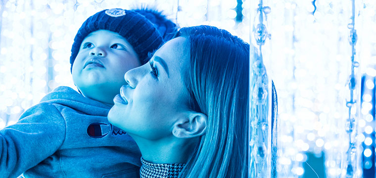 Woman and baby under blue lights.