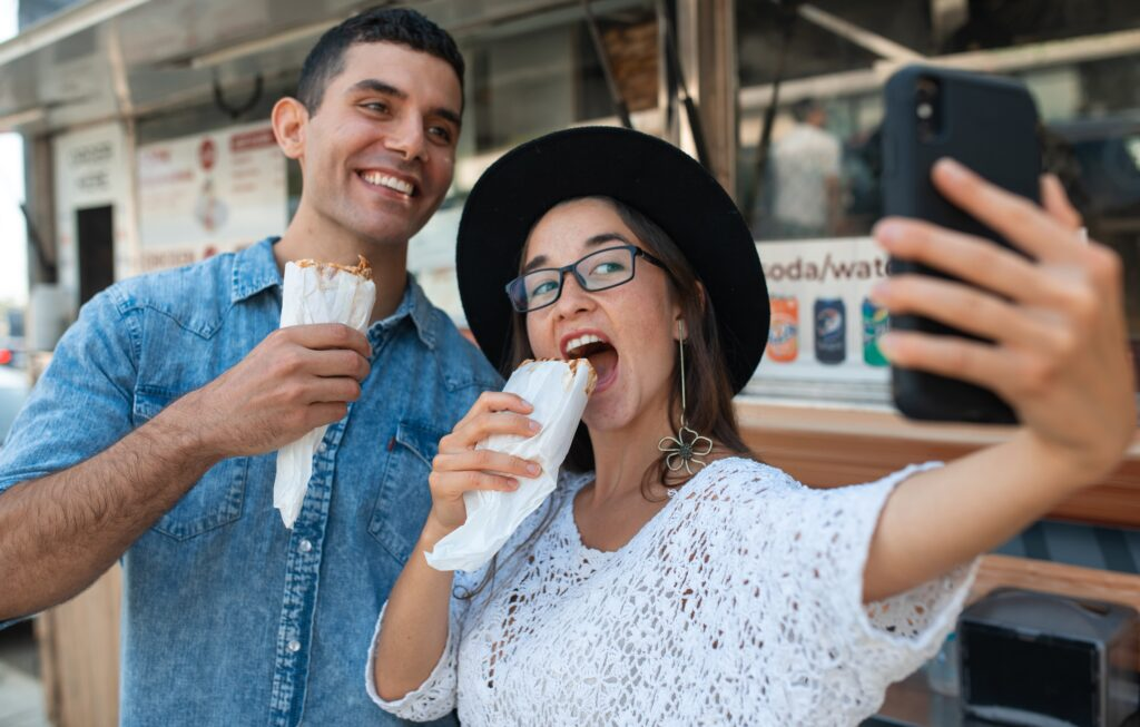 Smiling couple taking selfie in front of food truck.